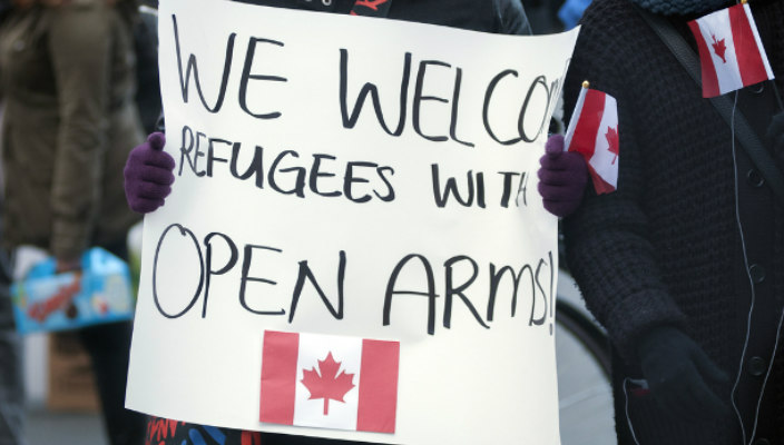 Sign welcoming refugees with a Canadian flag