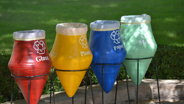 Colorful recycling bins against green grass