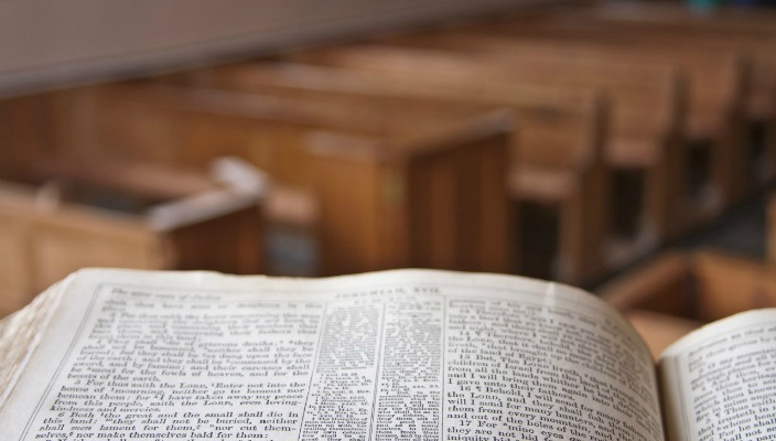 View of empty sanctuary pews from pulpit with Bible on it