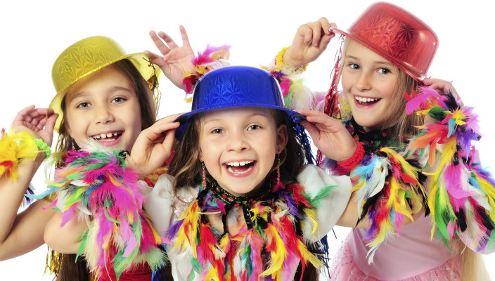 Three pre-teen girls in colorful hats and feathered boas